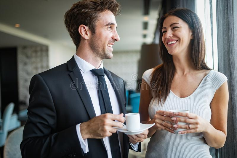 Pares novos bonitos que falam entre si e que sorriem ao apreciar o café imagem de stock