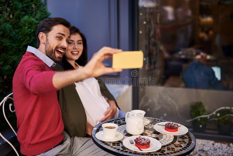 Pares novos bonitos que fazem o selfie no café exterior fotografia de stock royalty free