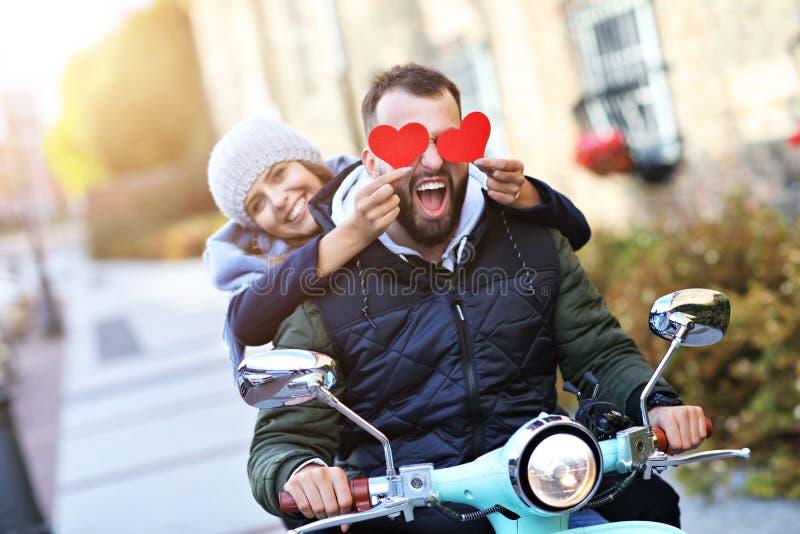 Pares novos bonitos que guardam corações ao montar o 'trotinette' na cidade no outono fotos de stock