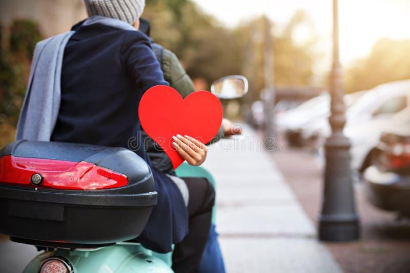 Pares novos bonitos que guardam corações ao montar o 'trotinette' na cidade no outono imagens de stock