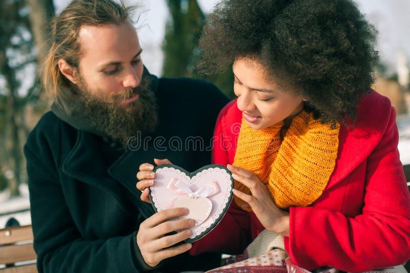 Pares novos bonitos que guardam um coração grande no dia de inverno imagem de stock royalty free