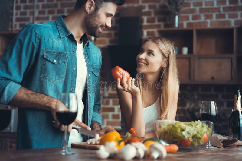Pares novos bonitos que preparam uma refeição saudável junto ao passar o tempo livre em casa fotografia de stock