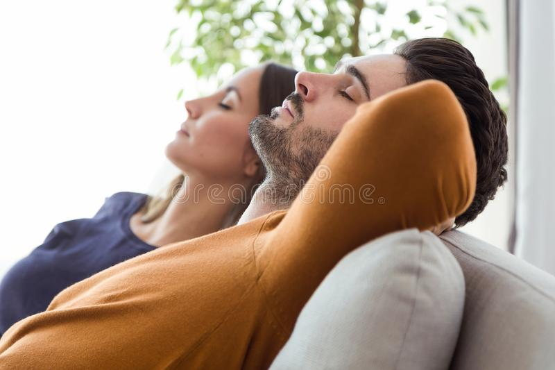 Pares novos bonitos que relaxam no sofá em casa imagem de stock royalty free