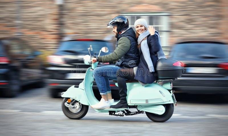 Pares novos bonitos que sorriem ao montar o 'trotinette' na cidade no outono foto de stock royalty free