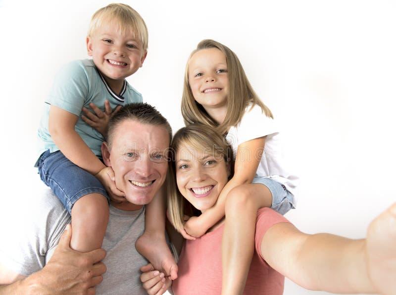Pares novos bonitos que tomam o autorretrato da foto do selfie com vara e o filho e a filha levando do telefone celular nos ombro imagem de stock