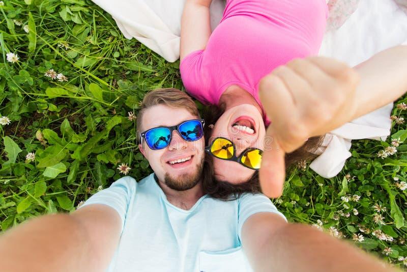 Pares novos caucasianos alegres que tomam o selfie que encontra-se em uma grama em um parque summertime imagens de stock royalty free