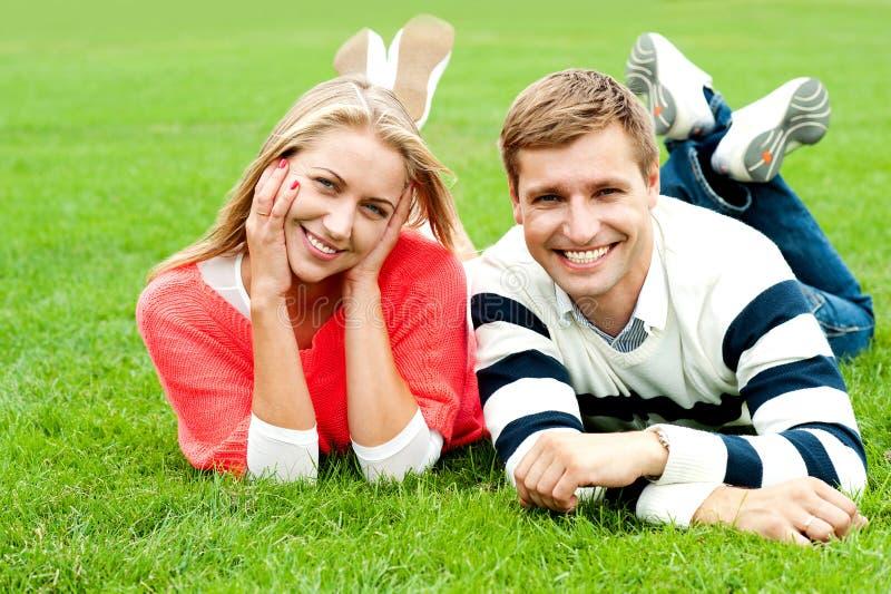 Pares novos Charming que encontram-se na grama verde fotos de stock royalty free