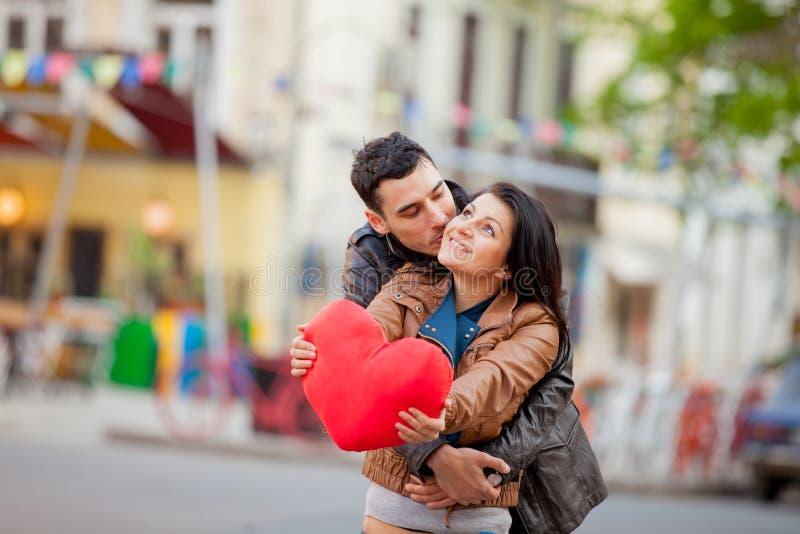 Pares novos com beijo do brinquedo da forma do coração imagens de stock