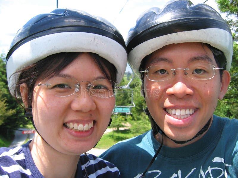Pares novos com capacetes fotografia de stock