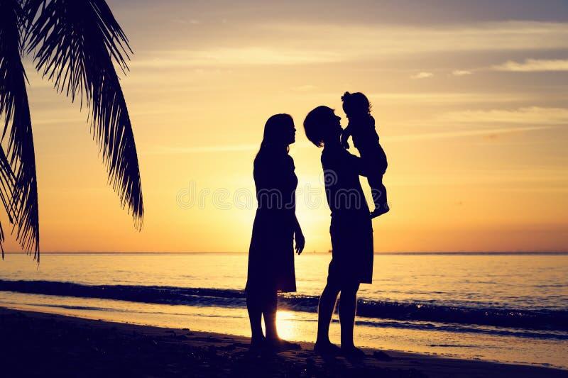 Pares novos com a criança pequena no por do sol tropical imagem de stock royalty free