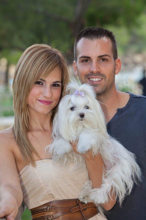 Pares novos com o cão maltês do animal de estimação imagem de stock royalty free