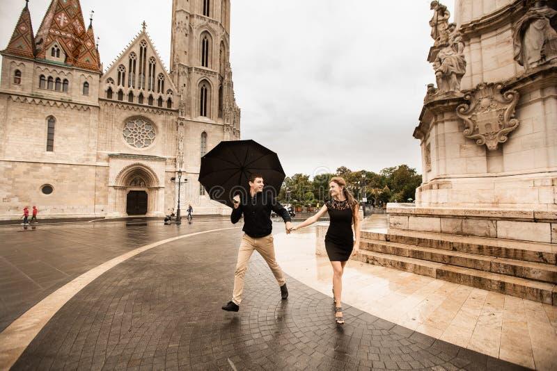Pares novos com o guarda-chuva que anda em Budapest em um dia chuvoso Hist?ria de amor fotos de stock
