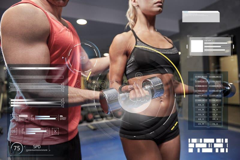 Pares novos com o peso que dobra os músculos no gym imagem de stock