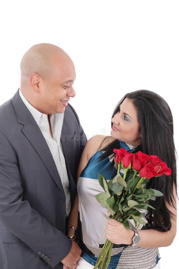 Pares novos com o ramalhete das rosas que olham se fotografia de stock royalty free