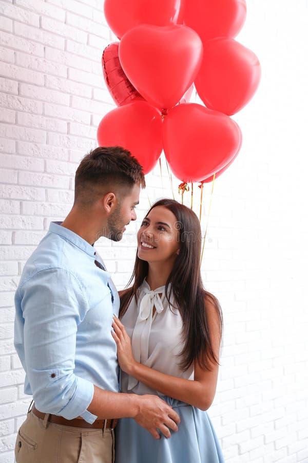 Pares novos com os balões de ar perto da parede de tijolo Celebra??o do dia do ` s do Valentim de Saint fotografia de stock
