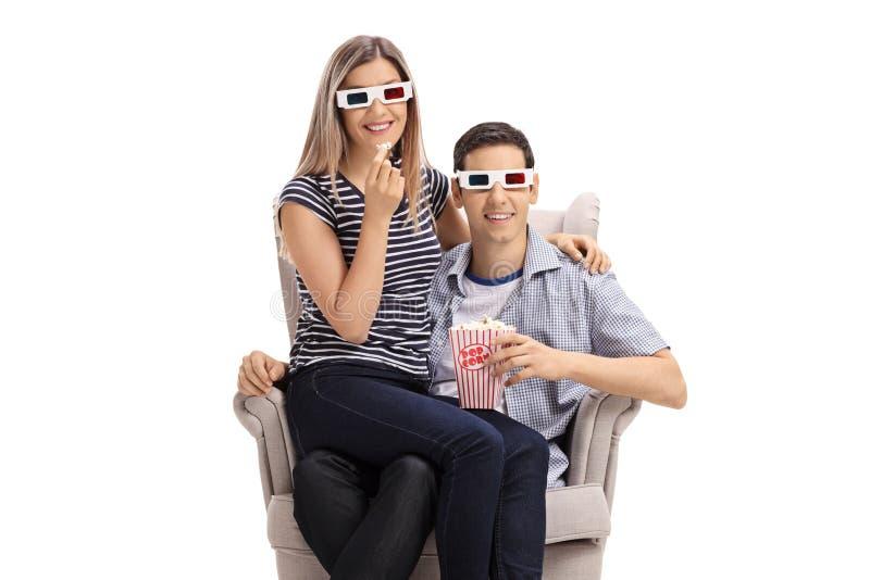 Pares novos com os vidros 3D e a pipoca que sentam-se em uma poltrona foto de stock royalty free