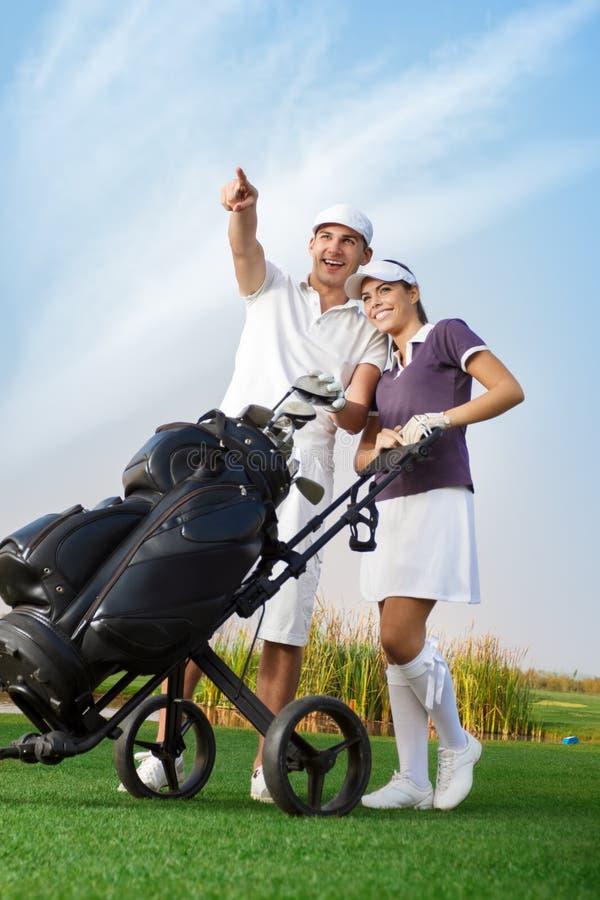 Pares novos com saco de golfe fotografia de stock royalty free