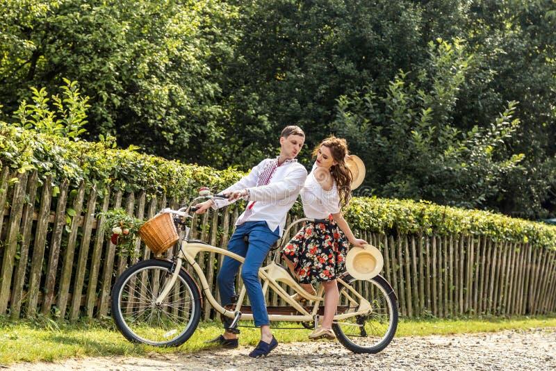 Pares novos com tandem da bicicleta no parque Os jovens mantêm chapéus em seus mãos e sorriso Na parte de trás da cerca da árvore imagem de stock royalty free