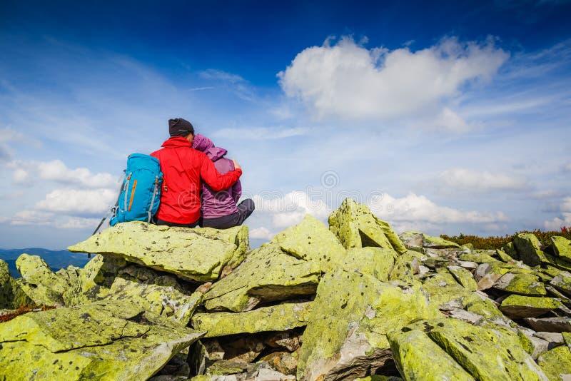 Pares novos com a trouxa que relaxa nas montanhas Alpinismo, estilo de vida saudável fotos de stock