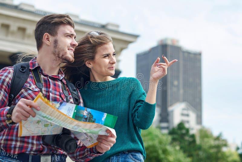 Pares novos com um mapa na cidade Cidade sightseeing dos turistas felizes com mapa fotografia de stock royalty free