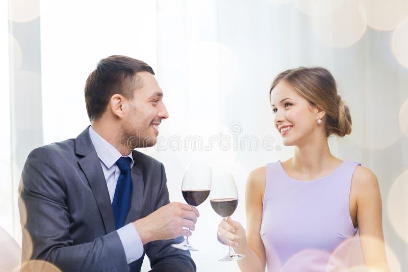 Pares novos com vidros do vinho no restaurante fotografia de stock