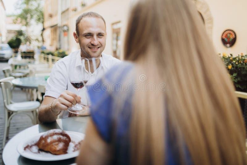 Pares novos com vidros do vinho tinto em um restaurante fotografia de stock royalty free