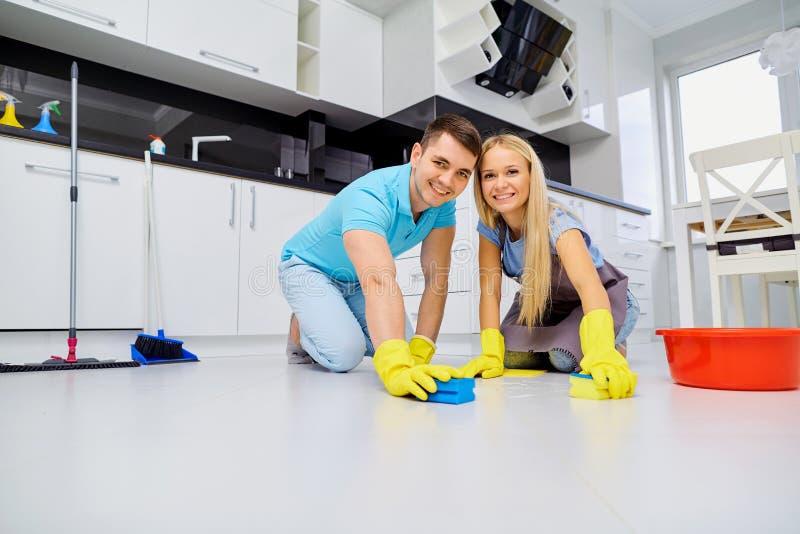 Pares novos da família que fazem a limpeza na cozinha fotografia de stock