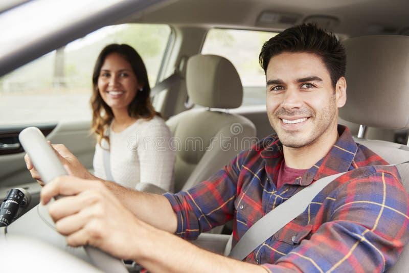Pares novos da raça misturada que conduzem no carro no feriado, retrato fotos de stock