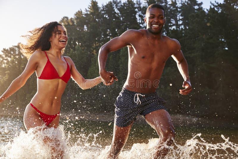 Pares novos da raça misturada que correm e que espirram em um lago fotografia de stock royalty free