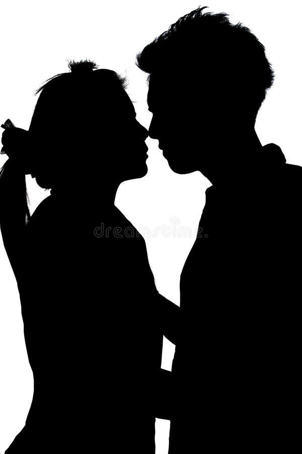 Pares novos da silhueta no amor imagens de stock
