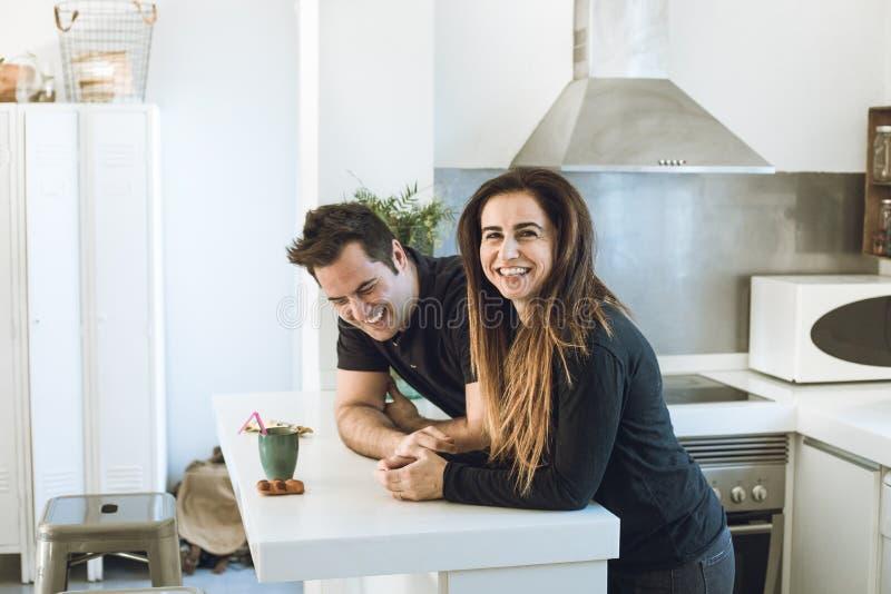 Pares novos de amantes que beijam e que abraçam na cozinha Homem e mulher que mostram a afeição e a ternura imagens de stock