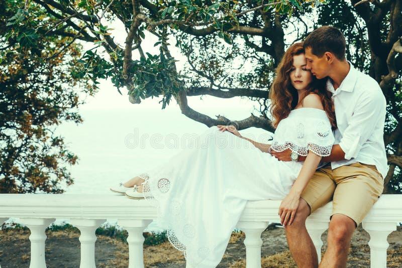 Pares novos de amantes que sentam-se em uma balaustrada, homem que abraça uma mulher Relaxe o conceito do estilo de vida junto imagem de stock