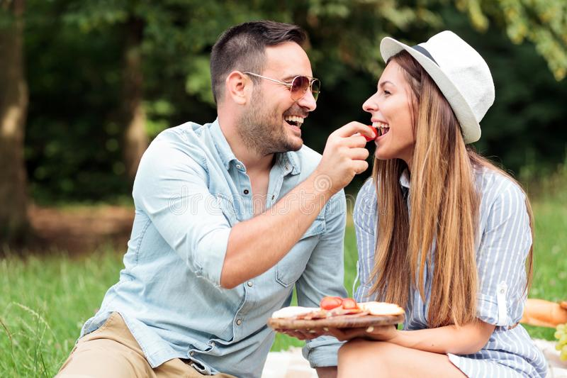 Pares novos de amor que apreciam seu tempo em um parque, tendo um piquenique rom?ntico ocasional fotografia de stock royalty free