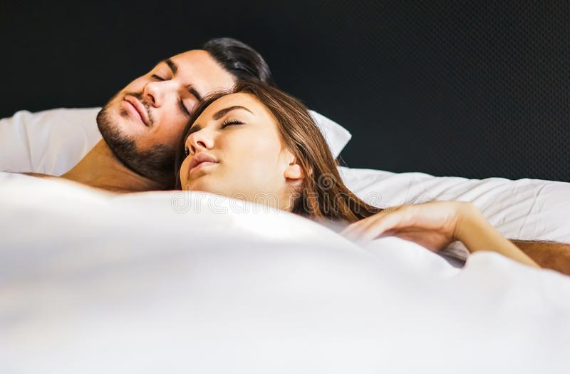 Pares novos de amor que dormem junto em uma cama com momentos da vida branca das folhas em casa - dos povos no amor no quarto imagens de stock