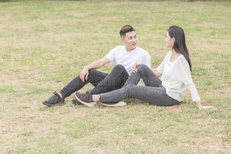 Pares novos de amor que sentam-se para baixo na grama imagens de stock