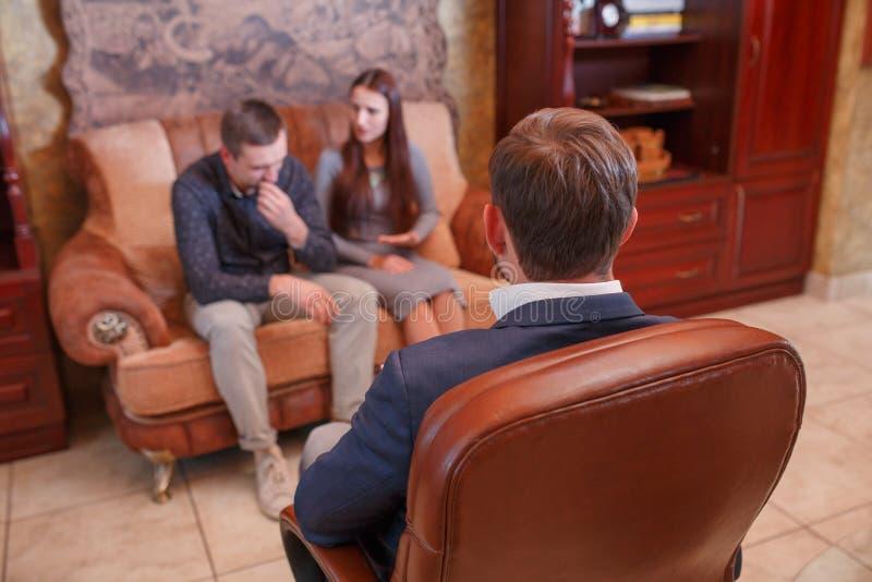 Pares novos de Beautiful do psicólogo que sentam-se no sofá quando o doutor tomar notas imagem de stock royalty free