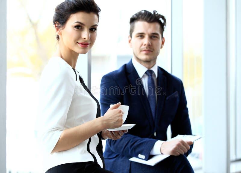 Pares novos de profissionais que conversam durante a ruptura de café imagem de stock