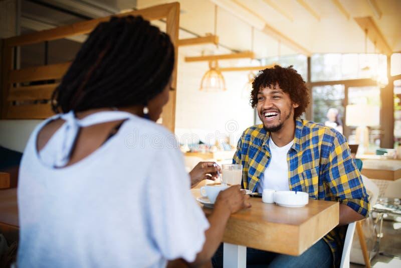 Pares novos de riso no café, tendo uma grande estadia junto fotografia de stock royalty free