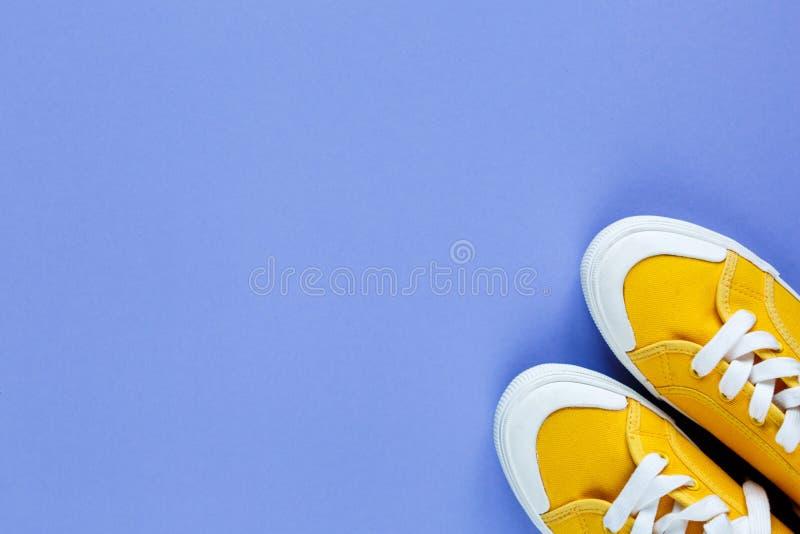 Pares novos de sapatilhas amarelas no fundo violeta Sapatilha do estilo de vida foto de stock