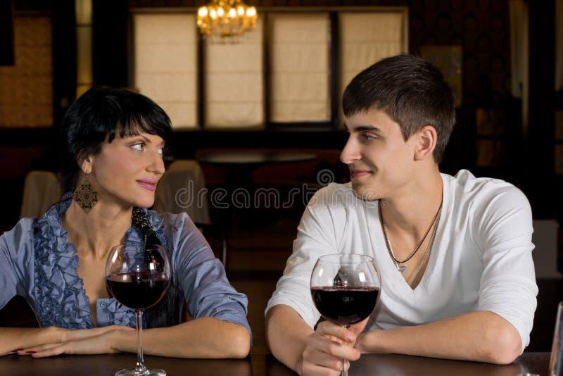 Pares novos de sorriso em uma data que bebe para fora fotografia de stock royalty free
