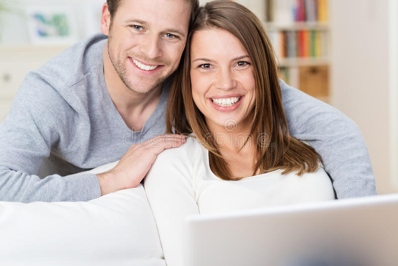 Pares novos de sorriso que compartilham de um laptop foto de stock royalty free