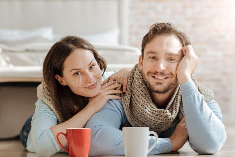 Pares novos de sorriso que expressam o amor em casa fotografia de stock