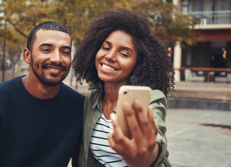 Pares novos de sorriso que tomam o selfie no telefone esperto foto de stock royalty free