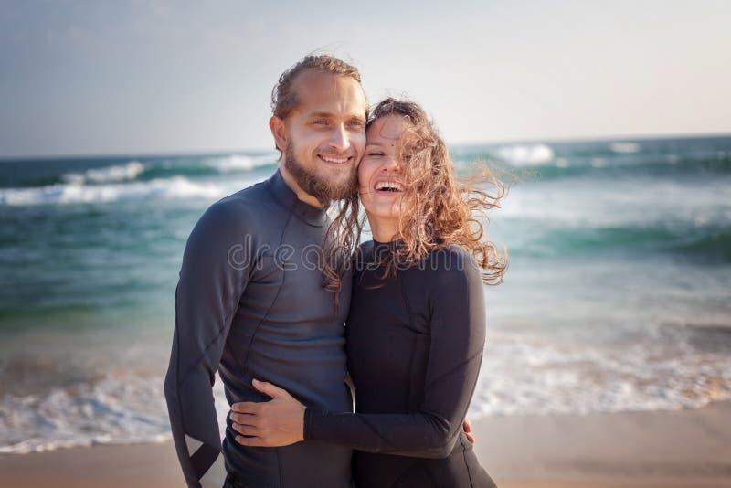 Pares novos de surfistas de sorriso felizes na costa do oceano, conceito do curso das f?rias do esporte fotografia de stock