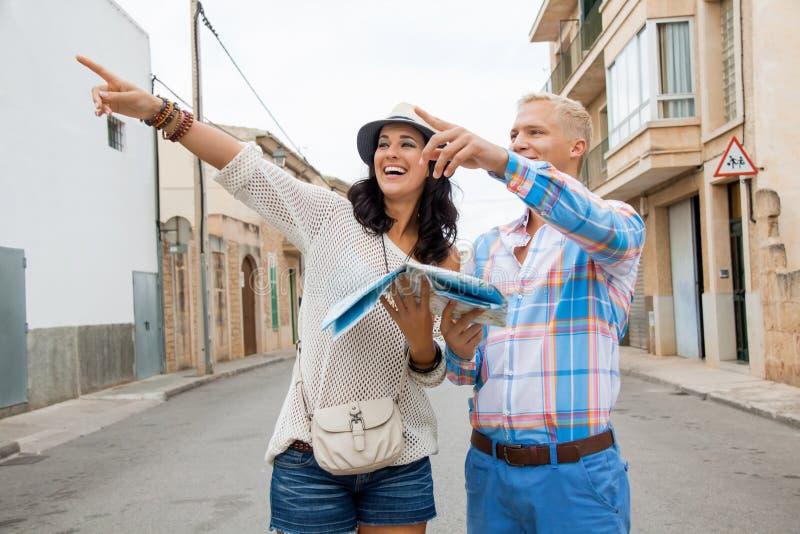Pares novos de turistas que consultam um mapa fotos de stock