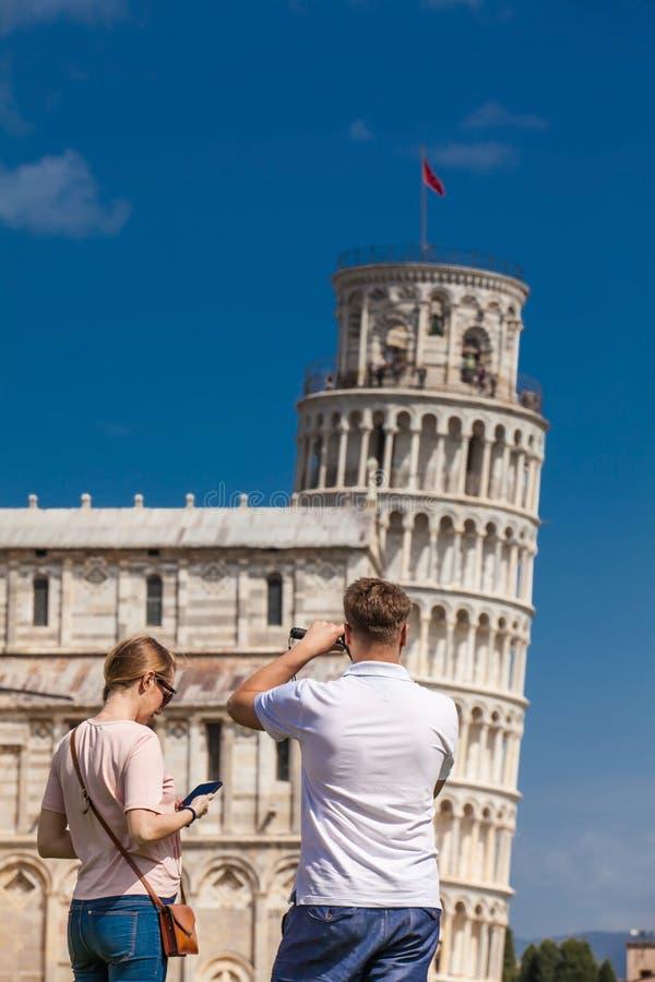 Pares novos de turistas que tomam imagens da torre inclinada famosa de Pisa fotos de stock