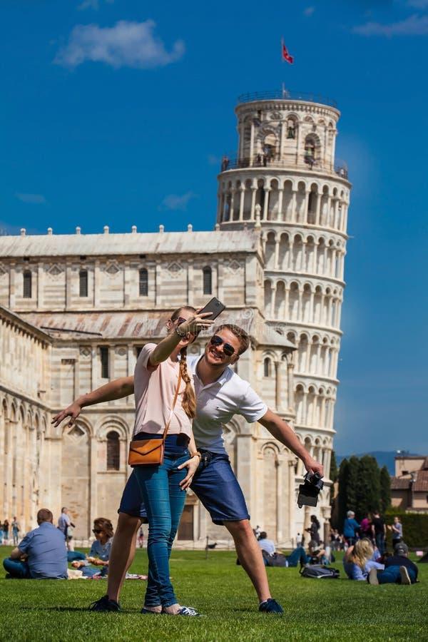 Pares novos de turistas que tomam um selfie na frente da torre inclinada famosa de Pisa imagem de stock royalty free