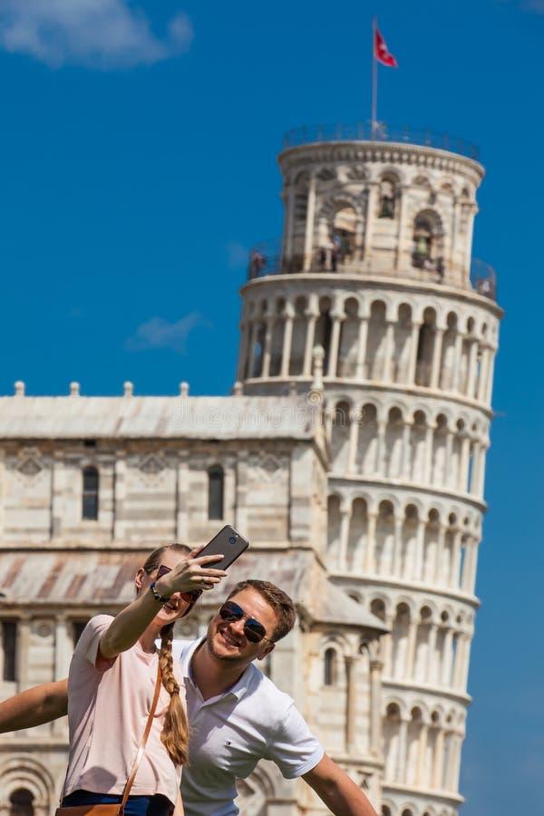 Pares novos de turistas que tomam um selfie na frente da torre inclinada famosa de Pisa fotos de stock royalty free