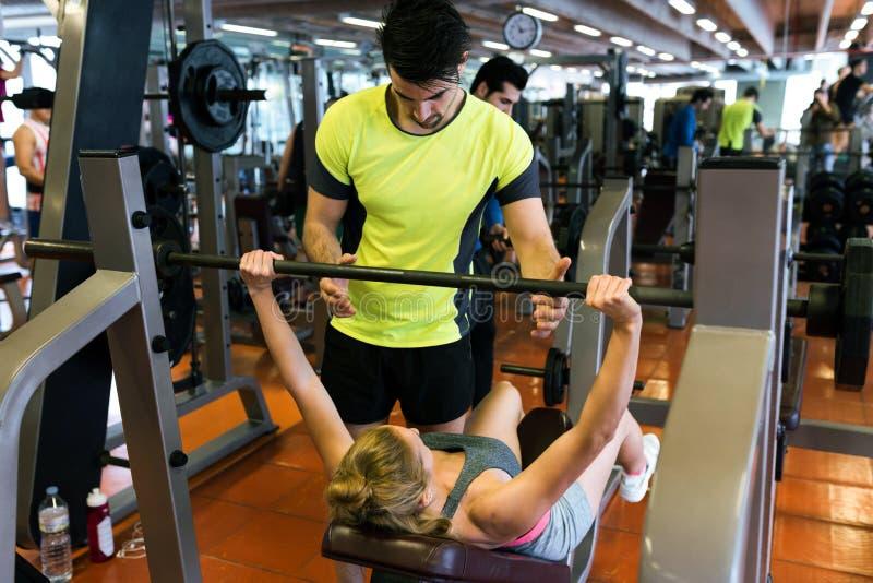 Pares novos desportivos que fazem o exercício muscular no gym imagem de stock royalty free