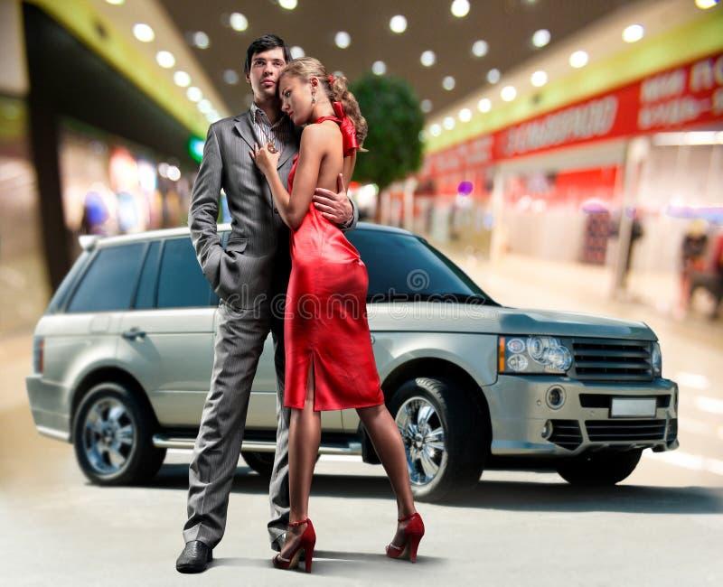 Pares novos do amor do retrato sob o carro Offroad fotografia de stock royalty free